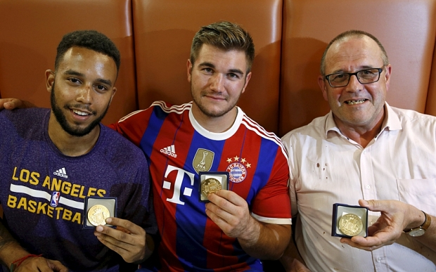 Sadler, Sharlatos, and Norman, three men who helped to disarm a Muslim terrorist on a train from Amsterdam to France, pose with their medals at a restaurant in Arras, France